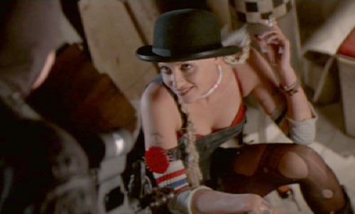 Tank Girl: Surprised by a soldier while on guard duty, Rebecca attempts to distract him with a little striptease.